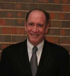 Dr. Michael Moats, DDS wearing a suit and tie, smiling