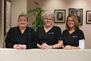 moats dental staff of 3, wearing black scrubs and smiling
